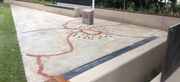 The memorial features exfoliated honey coloured granite with red and black honed, laser cut, granite inlay symbolising a poppy.
